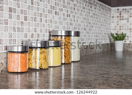 Food ingredients in glass jars on a kitchen counter top.