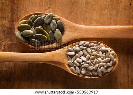 Food ingredients in wooden spoon on wooden background. Pumpkin seed and sunflower seed #550569919