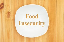 Food Insecurity message on white empty plate on a wood table