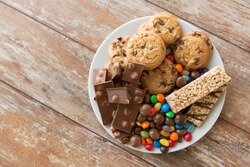 food, junk-food and unhealthy eating concept - close up of chocolate, oatmeal cookies, drop candies and muesli bars on plate