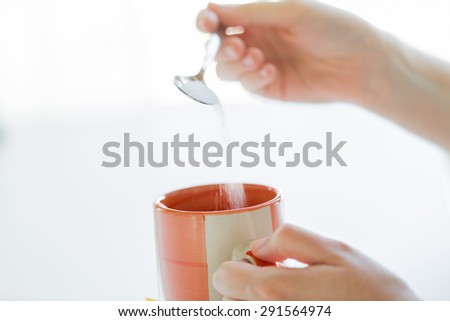 food, junk-food, drinks and unhealthy eating concept - close up of woman hands with spoon adding sugar to tea cup