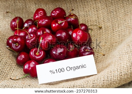 food labeling concept with bright red cherries and an organic label