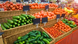Food market vegetables with blank price tag labels. Various fresh ripe cucumbers, tomatoes, peppers and other agriculture products on marketplace sale.