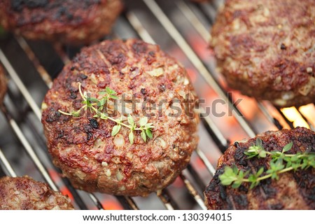 food meat - beef burgers on bbq  barbecue grill with flame. Shallow dof.
