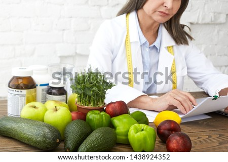 Food, nutrition, health, wellbeing and dietology concept. Elderly female nutritional expert with measuring tape around her neck developing dietary plan to improve eating habits of her client #1438924352