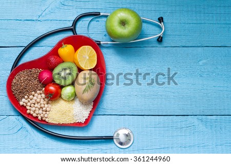 Food on heart plate with stethoscope cardiology concept on blue boards