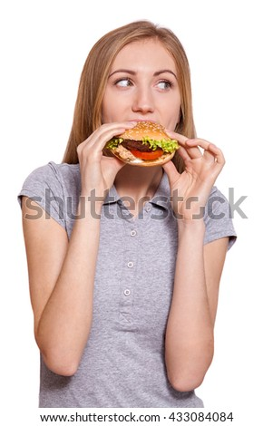 Food on the go.Closeup of a young caucasian woman eating a big hamburger, isolated on white background. #433084084