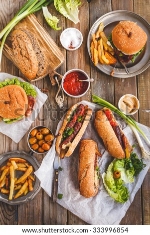 Food party table concept. Grill Sausage Sandwiches with two hamburger , potatoes fried and various sauce served on rustic table from above.