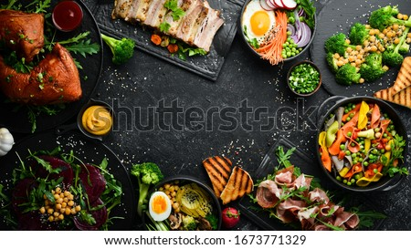 Food: pasta, pork ribs, avocado, Buddha bowl and beet salad on a black stone background. Top view. Free space for text.