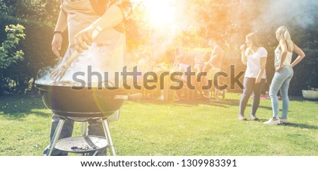 Food, people and family time concept - man cooking meat on barbecue grill at summer garden party