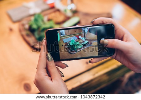 Food photography for social networks. Close-up image of female hands holding phone with food on screen taking picture of healthy meal