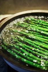 Food photography of asparagus spears blanching in a pan of hot water