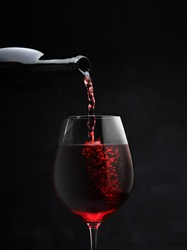 food photography of glasswine goblet front view with red wine pouring from a bottle for a romantic evening on a black background isolated close up