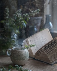 food photography of still life with a cup of hot herbal tea side view with an open book on a bright kitchen table with glass bottles in the background