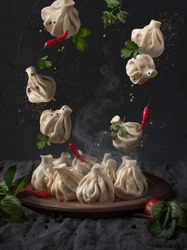 food photography of traditional georgian cuisine dish front view, levitating (flying) khinkali over a plate, together with chili peppers, parsley and spices on gray textured background close up