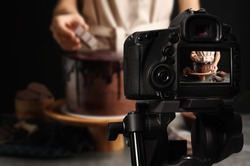 Food photography. Shooting of chef decorating chocolate cake, focus on camera