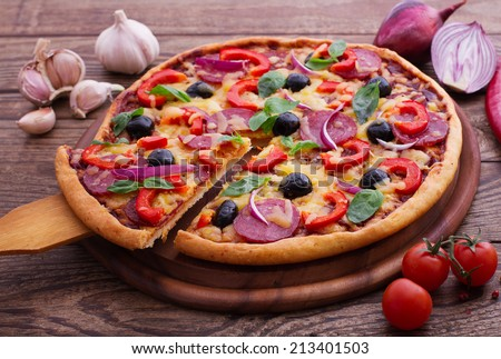 Food.  Pizza with tomato, salami and olives. Pizza with ham, pepper and olives. Delicious fresh pizza served on wooden table.