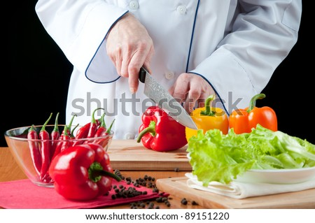 Food preparation – chef cutting bell peppers, over a black background