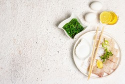 Food preparation concept. Pieces of raw hake, chukka salad, lemon wedge, fresh herbs, eggs, sea salt. Traditional Asian meal on light tones plaster background, top view