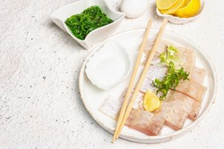 Food preparation concept. Pieces of raw hake, chukka salad, lemon wedge, fresh herbs, eggs, sea salt. Traditional Asian meal on light tones plaster background, copy space
