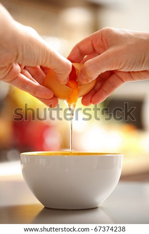 Food preparing, back view of hands cracking up a raw egg