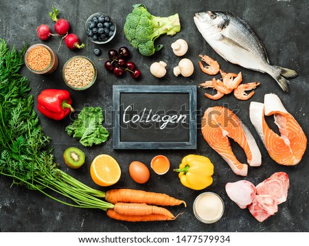 Food rich in collagen. Various food ingredients and chalkboard with Collagen letters over dark background. Top view or flat lay