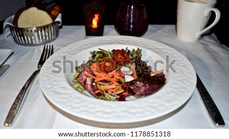 Food served on board of business class in airplane : Fresh Salad with choice of salad dressing, serve in early morning, still dark. #1178851318