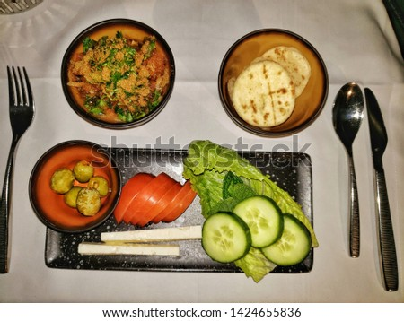 Food served on board of business class in airplane : Traditional Arabic breakfast-feta cheese, cucumber, tomato and olives in dark background  #1424655836
