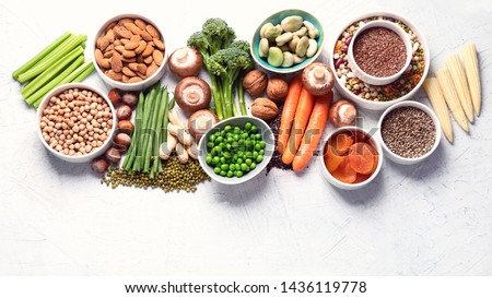 Food sources of plant based protein. Healthy diet with  legumes, dried fruit, seeds, nuts and vegetables.  Foods high in protein, antioxidants, vitamins and fiber. Image with copy space. Top view