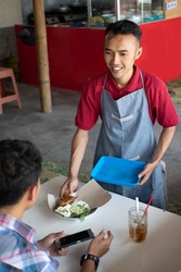 Food stall waiters are happy to serve customers by serving orders on trays at the stall