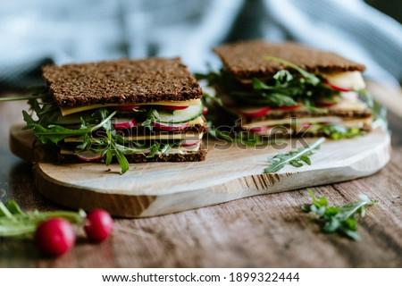Food still life, fresh whole grain bread with cheese, radish, cucumber, arugula, healthy food, superfood Stock photo ©