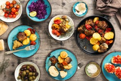 Food table, fried meat with vegetables in a pan, salad and appetizers, top view