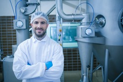 Food technician smiling at camera in a food processing plant