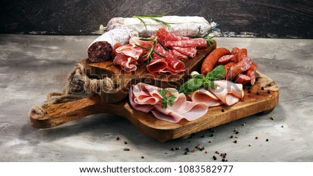 Food tray with delicious salami, ham,  fresh sausages and herbs. Meat platter with selection. Сток-фото ©