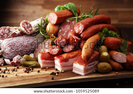 Food tray with delicious salami, ham,  fresh sausages, cucumber and herbs. Meat platter with selection
