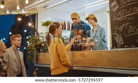 Food Truck Employee Hands Out a Freshly Made Burger to a Happy Young Female. Young Lady is Paying for Food with Contactless Credit Card. Street Food Truck Selling Burgers in a Modern Hip Neighbourhood