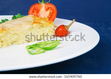 food : vegetable casserole triangle on white plate with pepper and tomatoes on blue table - stock photo