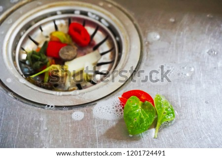Food waste from the washing up in the sink and trash traps grid of drainage holes. #1201724491