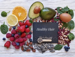 Foods for healthy long hair. Best beauty foods for shiny, strong hair. Concept of hair growth food. Fresh berries, citrus fruit, almond, avocado, spinach, beans, eggs, sunflower and chia seeds.