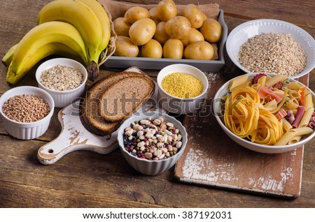 Foods high in carbohydrate on rustic wooden background. Top view