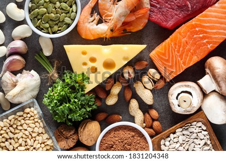 Foods High in Zinc as salmon, seafood-shrimps, beef, yellow cheese, parsley leaves, mushrooms, cocoa, pumpkin seeds, garlic, bean, almonds, pine nut. Top view