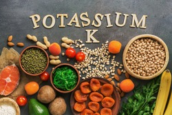 Foods rich in potassium, salmon, legumes, vegetables, fruits on a dark background. Healthy food concept,avitaminosis prevention. Top view, flat lay