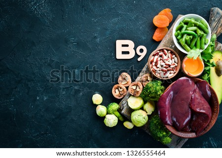 Foods that contain natural vitamin B9: Liver, avocado, broccoli, spinach, parsley, beans, nuts, on a black stone background. Top view.
