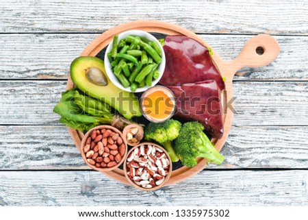 Foods that contain natural vitamin B9: Liver, avocado, broccoli, spinach, parsley, beans, nuts, on a white wooden background. Top view.
