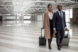 Fool of joy. Full length portrait of happy elegant business partners are walking along airport lounge while carrying luggage. They are looking ahead with smile. Copy space in the left side