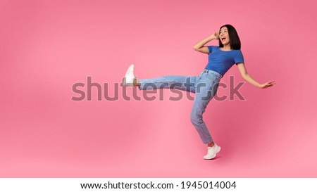 Fooling Around. Full length shot of ecstatic young asian lady jumping, dancing and raising leg up, being in a good mood, celebrating victory, bright pink studio background, free copy space, panorama Foto stock ©