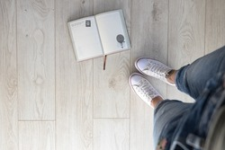Foot and legs seen from above and travel journal on wood floor. Traveling concept