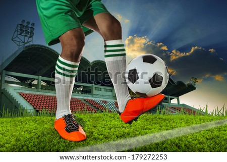 foot ball player holding foot ball on leg ankle in soccer sport field against stadium and dusky sky use for sport soccer football team competition match
