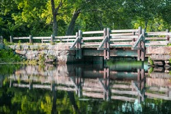 Foot Bridge On A Pond in Connecticut with  reflections of the bridge and forest on the water
