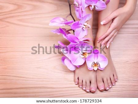 Foot care. Pedicure with pink orchid flowers on wooden background. Beautiful female feet and hand with french manicure. Spa